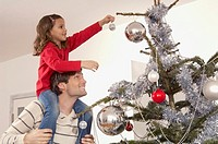 Father and daughter decorating a Christmas tree