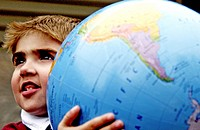 Close-up of a young boy holding a large globe