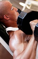 Close-up of a young man lifting bar bells in a gym
