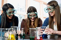 Three students with beakers laughing in a science lab