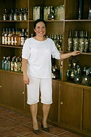 Mature woman standing near a shelf and smiling in a cafe