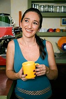 Mid adult woman holding a cup of coffee and smiling in a cafe
