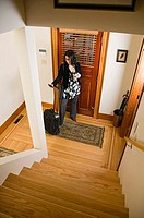 High angle view of a businesswoman standing by a door with luggage