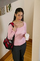 High angle view of a businesswoman holding a bag and a disposable cup