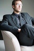 Businessman with glasses sitting on the couch thinking