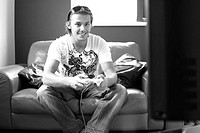 Man sitting on the couch playing video game console