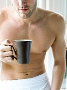 Man with towel holding a cup of coffee