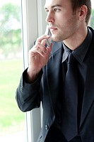 Businessman looking out of the window while talking on the mobile phone