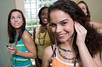 Teenage girl listening to music with her friends in the background