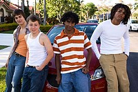 Two teenage boys and two young men leaning against a car