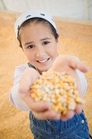 Pacific Islander girl standing in corn silo holding up handful of corn