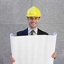 Businessman in hardhat holding blueprints