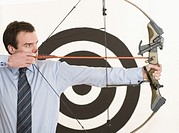 Businessman taking aim with a bow and arrow, with target in background