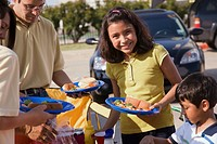 Girl 9-11 holding plate of food at tailgate party