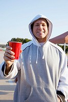Man holding red cup at tailgate party