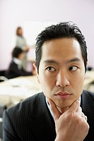 Asian businessman with chin in hand