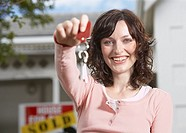 Woman with keys standing in front of house with sold sign