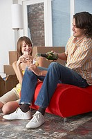 Couple with champagne in house with red chair celebrating (thumbnail)