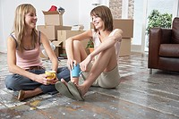 Two women sitting on hardwood floor with mugs and cardboard boxes smiling