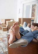 Man and woman lying down on sofa in home with cardboard boxes