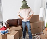 Man with lamp shade on head in home with cardboard boxes
