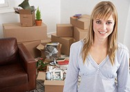 Woman in home with cardboard boxes smiling