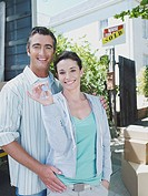 Man with arms around woman holding keys outdoors with sold sign on house