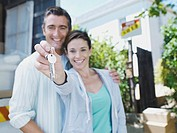 Man and woman with keys outdoors with moving van and sold sign on house smiling