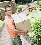Man carrying cardboard box outdoors with sold sign on house