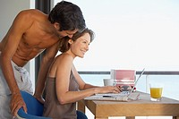 Woman at laptop and man in room with large windows