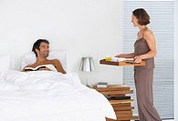 Woman bringing breakfast to man in bed