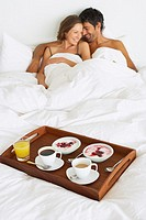 Woman in man in bed with breakfast tray