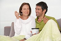 Man and woman on sofa eating ice cream smiling