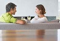 Man and woman sitting on sofa with glasses of wine