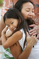 Asian mother hugging daughter