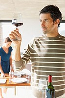 Man with red wine in glass and woman in background