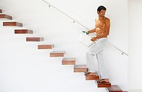 Man walking up stairs with laundry basket