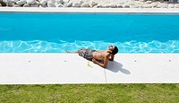 Man sunbathing with feet in pool