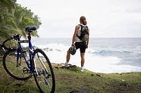 Male cyclist standing on cliff over ocean