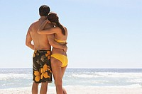 Rear view of man and woman in swimsuits embracing outdoors