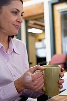 Businesswoman holding coffee cup, smiling