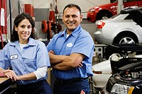Female and male auto mechanics in auto repair shop