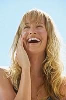 Closeup of woman applying sunblock to cheeks laughing