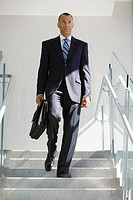 Mature businessman walking down steps carrying briefcase, low angle view