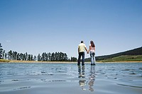 Man and woman standing on water holding hands