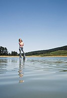 Woman standing on water with cell phone