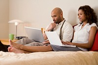 African couple typing on laptops