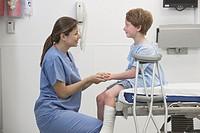 Nurse holding hand of boy with broken leg