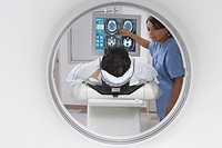 Patient in MRI scanner with Indian nurse explaining scan