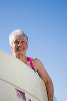 Senior woman carrying surfboard, waist up